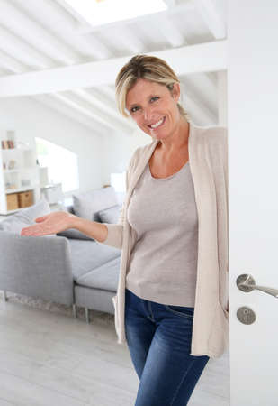 Mature woman welcoming people to come inside her home Stock Photo