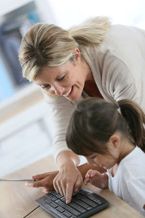 computer class: Teacher with little girl in class using computer and tablet