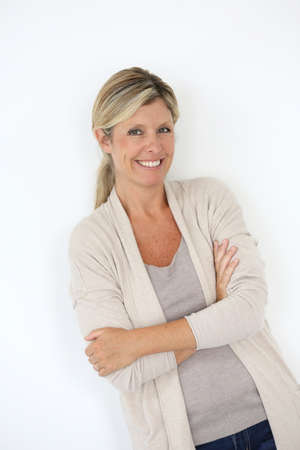 Mature blond woman standing on white background