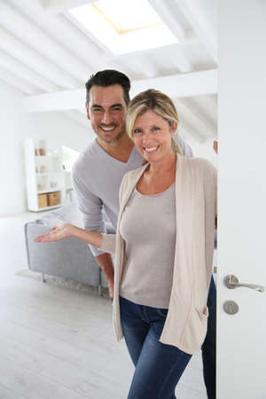 inviting: Cheerful mature couple standing at home front door Stock Photo