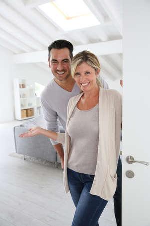 Cheerful mature couple standing at home front door Standard-Bild