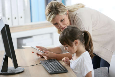 Teacher with little girl in class using computer and tablet photo