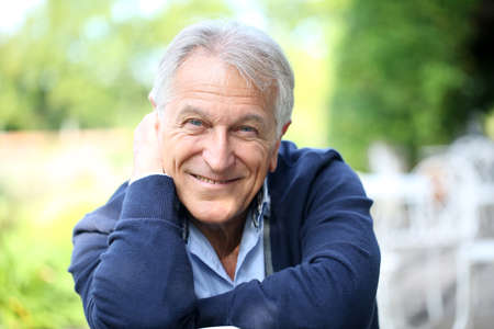 Portrait of senior man sitting in home garden Stock Photo
