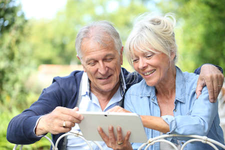 retiring: Senior couple connected on digital tablet