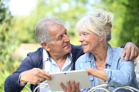 Senior couple connected on digital tablet photo