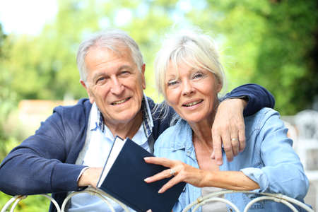 Senior couple relaxing in garden and reading book photo