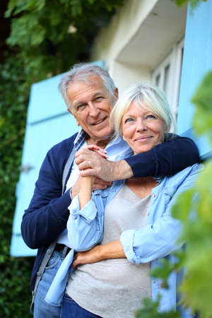 Senior man embracing his wife at house front door photo