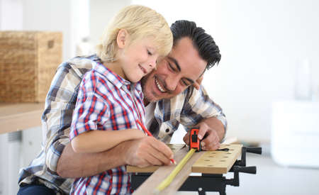 Father with kid measuring wood plank Stockfoto
