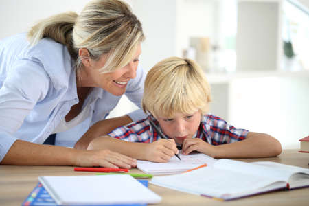 Mom helping little boy to do homework Stock Photo