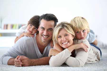 adult family: Portrait of happy family laying on carpet