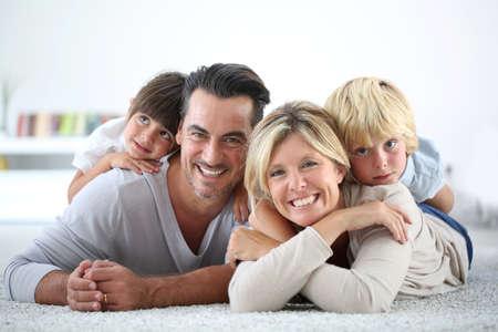 Retrato de família feliz que coloca no tapete