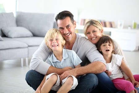 woman sitting floor: Portrait of happy family sitting on floor Stock Photo