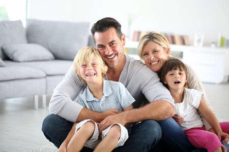 Portrait of happy family sitting on floor Foto de archivo