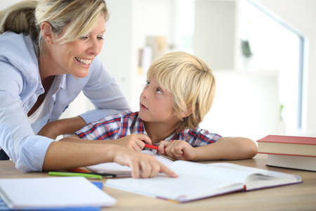 blonde mom: Mom helping little boy to do homework Stock Photo