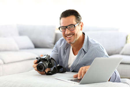 自宅の男の reflex カメラとラップトップを使用してください。