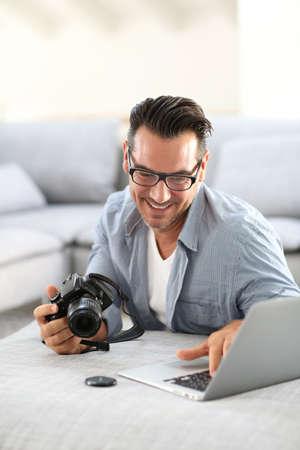 amateur: El hombre en su casa usando una cámara digital y un ordenador portátil