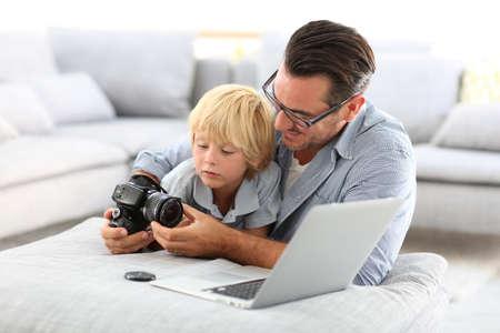 reflex: L'uomo con il ragazzino che gioca con la macchina fotografica reflex