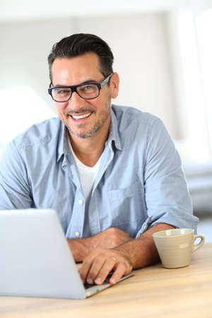 Portrait of mature man working on laptop photo