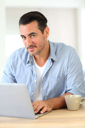 Portrait of mature man working on laptop photo