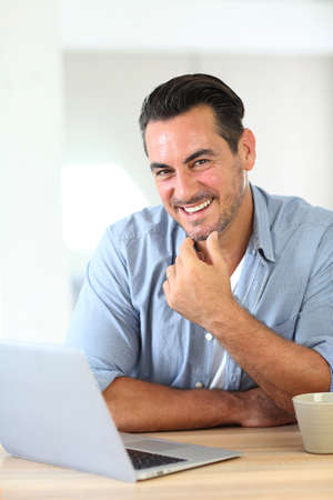 Mature man working at home with laptop photo