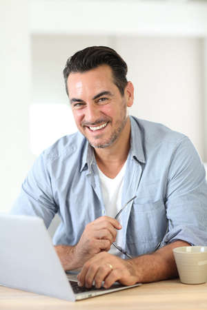 Portrait of mature man working at home with laptop photo