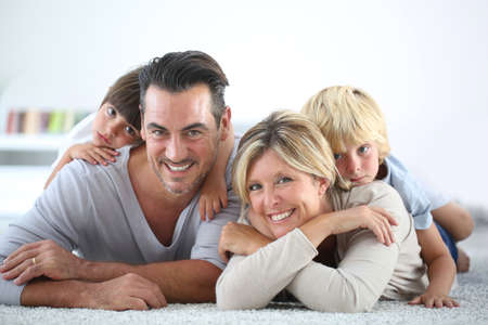 4 people: Portrait of happy family laying on carpet