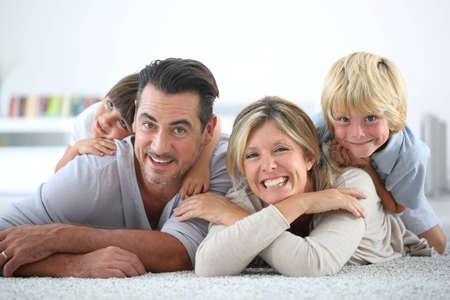 Portrait of happy family laying on carpet photo