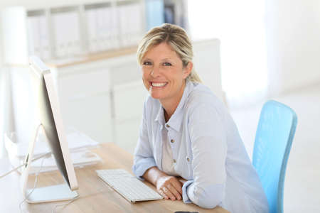 officeworker: Mature businesswoman sitting in front of desktop Stock Photo