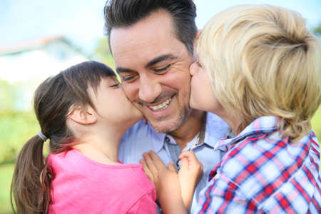 Portrait of kids giving a kiss to their daddy Stock Photo