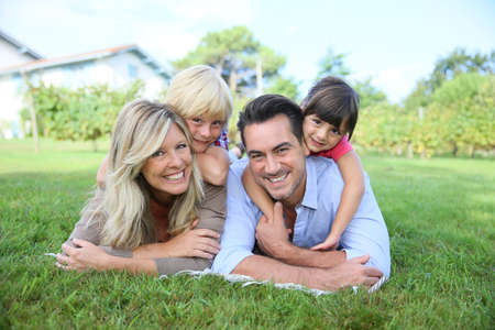 Family of four laying on grass in front of house photo