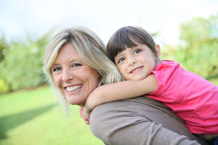 piggyback ride: Mother giving piggyback ride to little girl Stock Photo