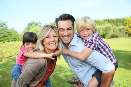 7 years old: Parents giving piggyback ride to kids in park Stock Photo