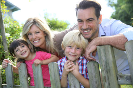 family garden: Happy family leaning on fence by country home Stock Photo