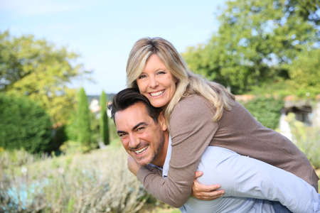 shoulder ride: Cheerful mature man giving piggyback ride to woman Stock Photo