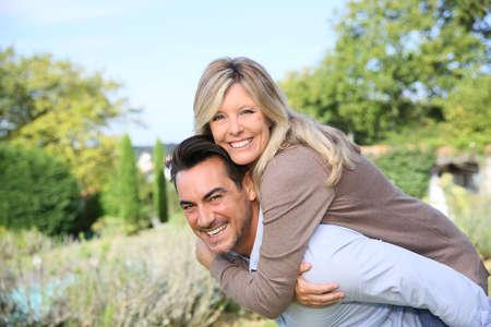 hombres maduros: Hombre maduro alegre que da a cuestas paseo a la mujer
