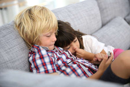 kids playing video games: Kids sitting in sofa and playing with smartphone