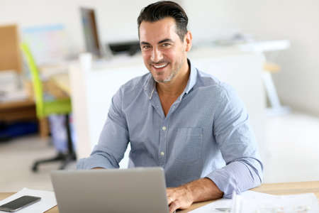 Businessman sitting in office and working on laptop