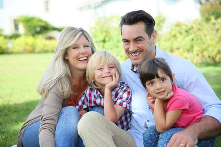 Portrait of happy family of four sitting in yard photo
