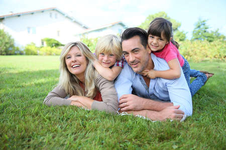 Family of four laying on grass in front of house Stock Photo