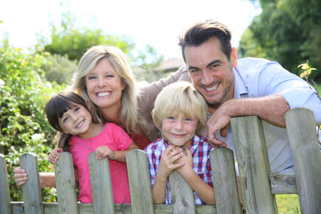 Happy family leaning on fence by country home Stock Photo