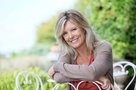 cadeira: Retrato da mulher de sorriso loura madura no jardim Imagens