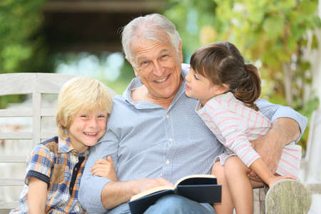grandkids: Senior man reading book with grandkids