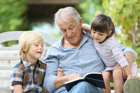 grandfather: Senior man reading book with grandkids