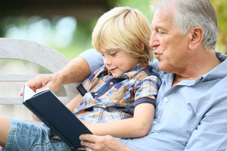 Grandfather reading book with grandson photo