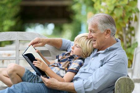 Dědeček čtení knihy s vnukem Reklamní fotografie