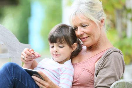 grandkid: Senior woman with grandkid playing game on smartphone
