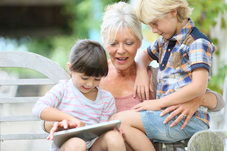 Grandmother with kids playing games on tablet photo