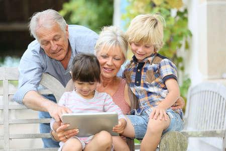 Glückliche Großeltern spielen Spiel auf Tablette mit Kindern