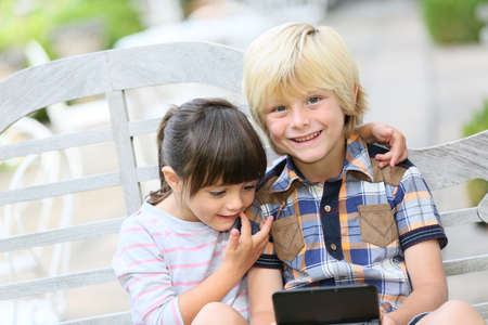 kids playing video games: Kids sitting on outdoor bench and playing video games Stock Photo