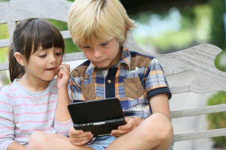 jugando videojuegos: Niños sentados en el banco al aire libre y juegos de video